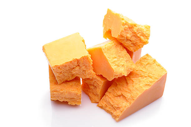 Roughly cut pieces of yellow cheese, maybe cheddar Blocks of Cheese on White Background cheddar cheese stock pictures, royalty-free photos & images