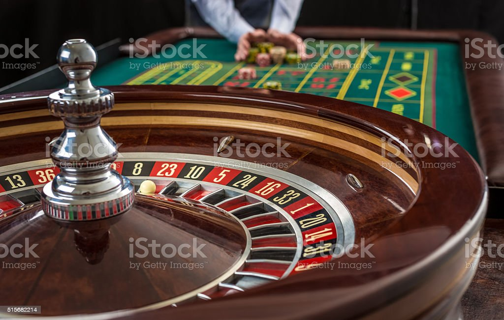 Roulette and piles of gambling chips on a green table. stock photo