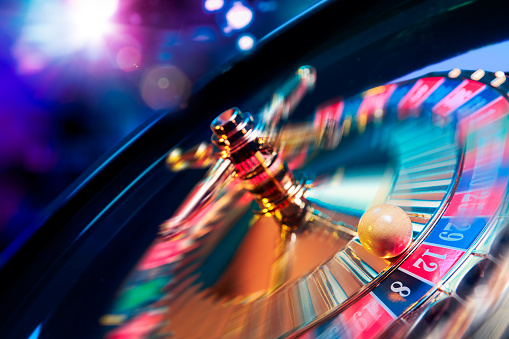 Roulette wheel in motion with a bright and colorful background