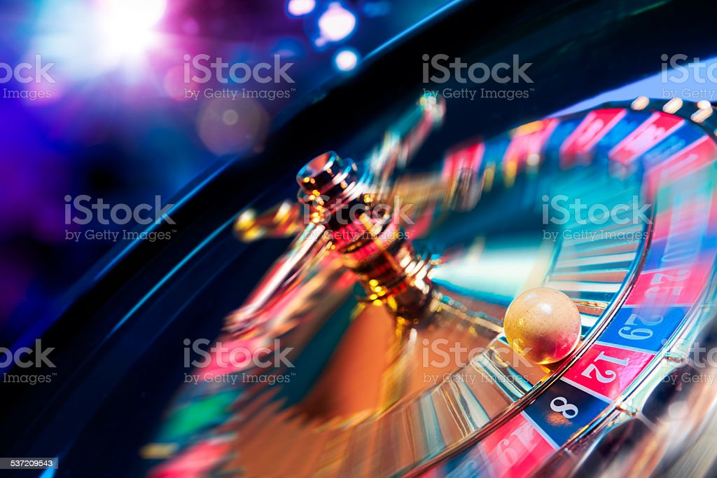 Roulette wheel in motion with a bright and colorful background stock photo