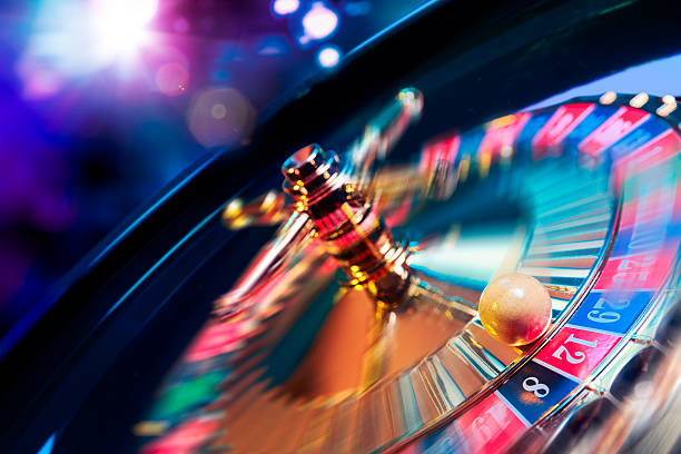 roulette wheel in motion with a bright and colorful background - gaming stockfoto's en -beelden