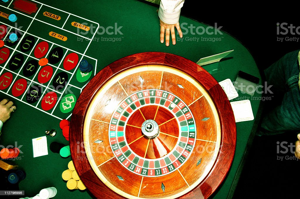 Roulette wheel with hand and table stock photo
