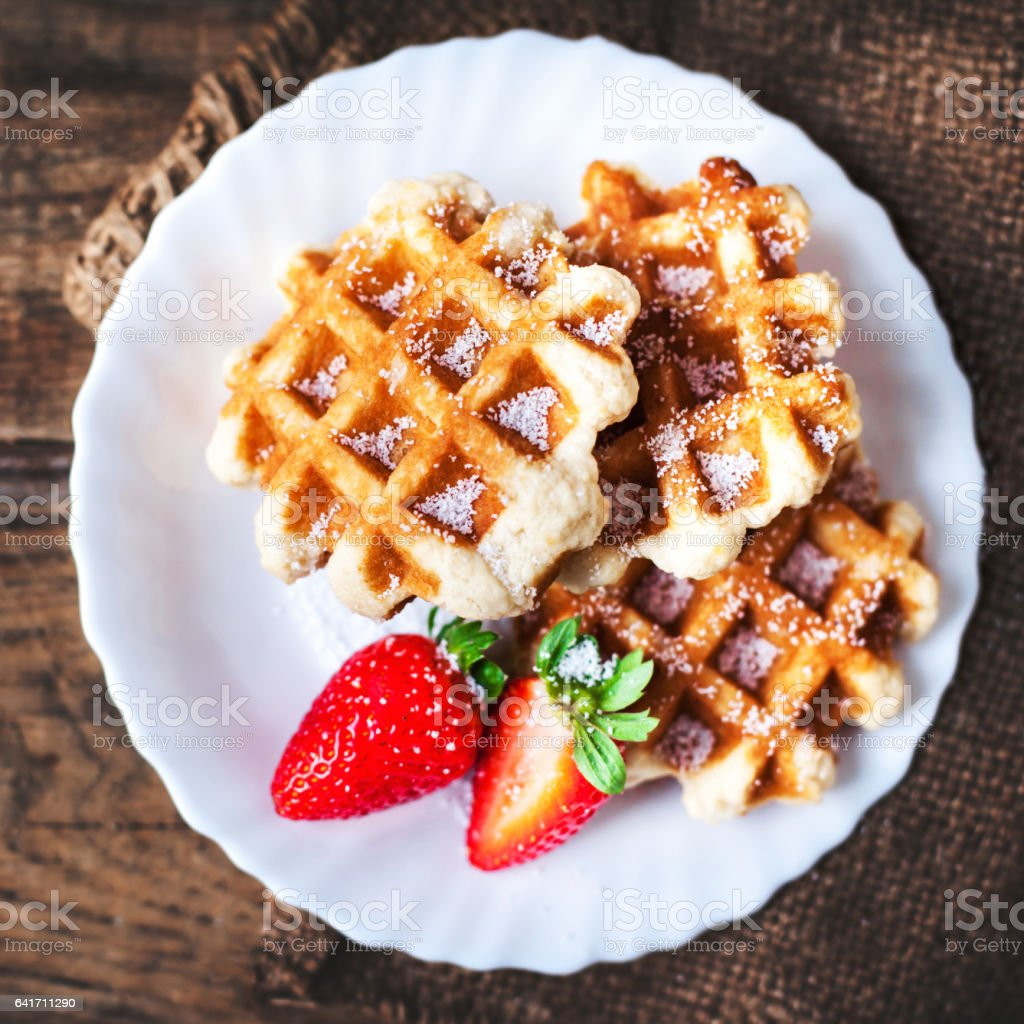 Round Belgian waffles with strawberries and icing on a white plate with copy space stock photo