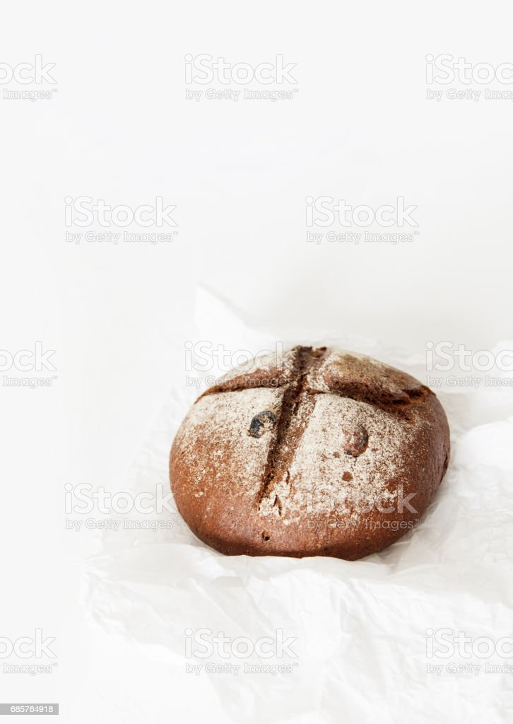 Round black bread lies on crumpled white paper on a white backgr foto stock royalty-free