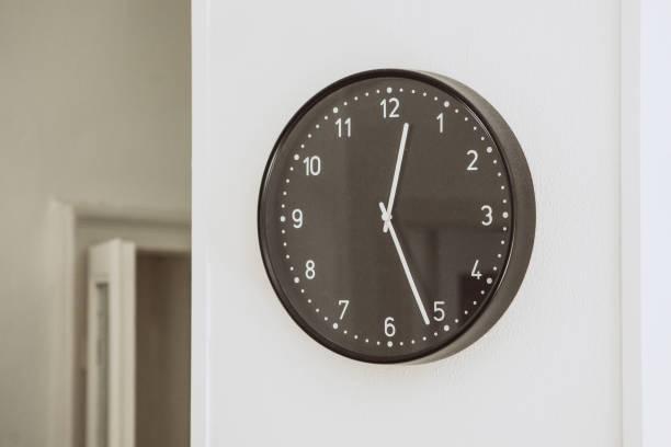 Runde schwarze Uhr an der weißen Wand – Foto