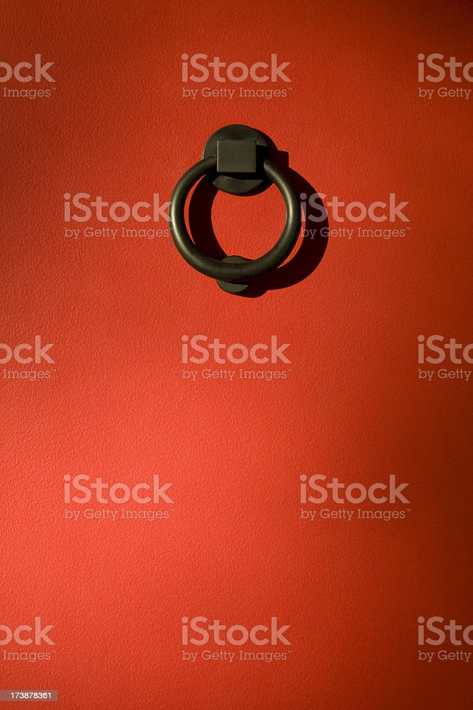 Round black iron knocker on red door. stock photo