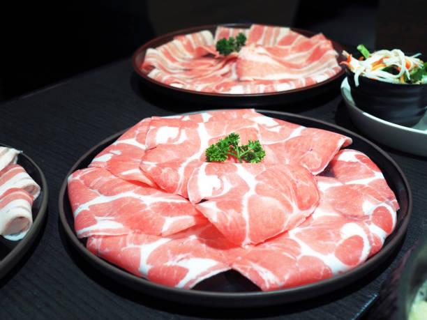 eine runde schwarze platte dünn geschnittenes schweinefleisch (schweinekamm oder schweineschulter klinge) vorbereitet für sukiyaki, shabu oder japanischen hot pot. - schmale schulter stock-fotos und bilder