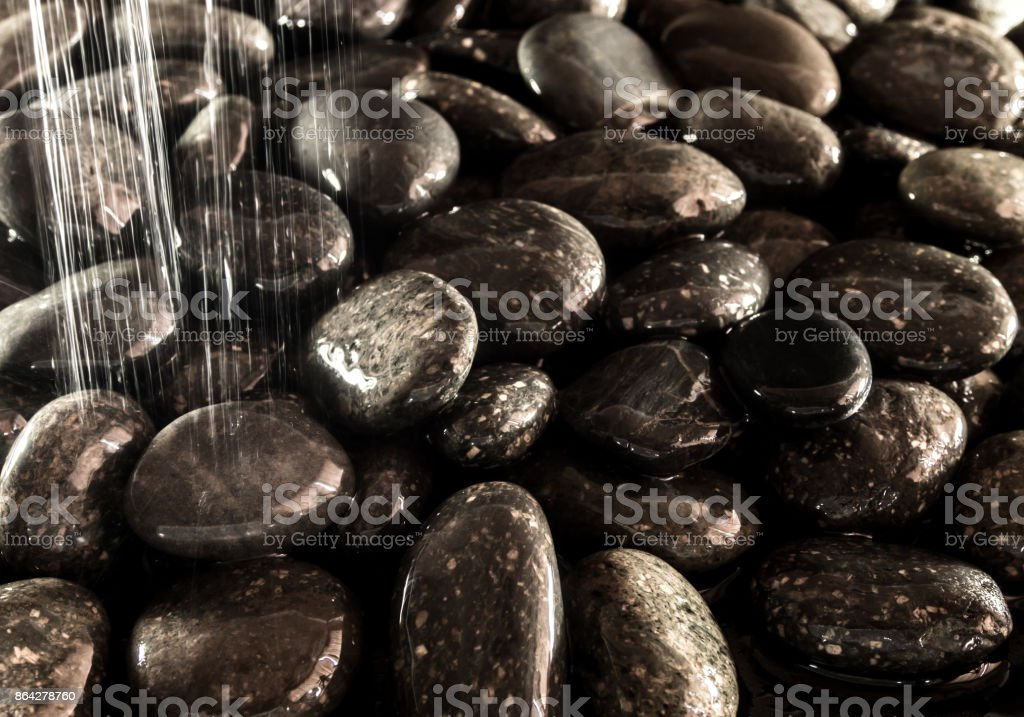 Round black stone on ground beside the waterfall royalty-free stock photo