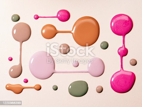 Nail polish rounded swatches on neutral beige background. Closeup of paint spills. Creative composition of various nail polish drops for manicure.