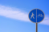 Round blue sign Pedestrian and bicycle path with combined path on the background of a beautiful cloudy sky