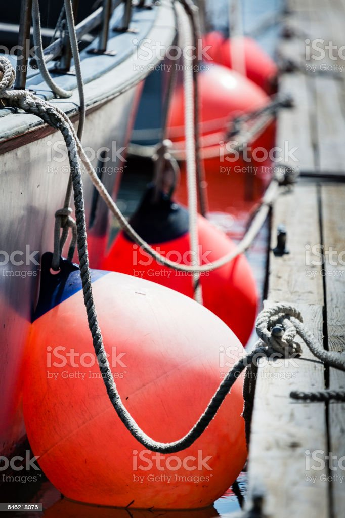 Round boat fenders between boat and dock stock photo