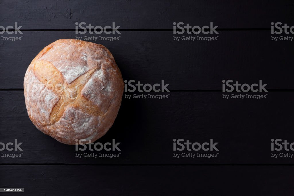Round bread on a black background, bread from a stove on dark boards, dough for designer, copy space, rustic style, minimalism, top view, bakery, art stock photo