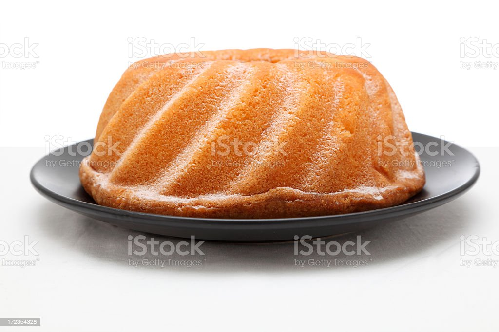 round cake in black plate on textured surface isolated stock photo