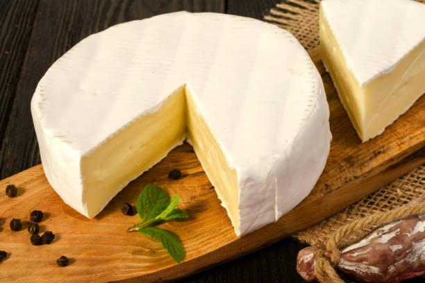 redondo de queso camembert, en rodajas, en una salchicha madera junta y fuet, sobre una plancha de madera, con saco. - fuet sausages fotografías e imágenes de stock