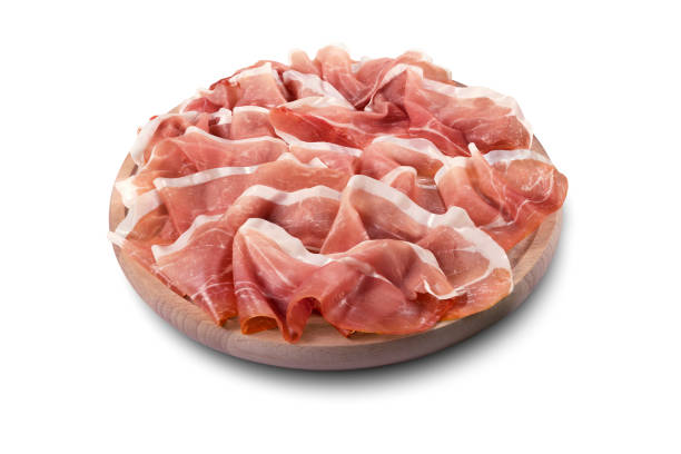 Round chopping board with sliced Parma ham stock photo