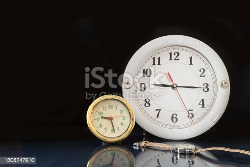 A round clock on a glass table with a reflection. Close-up objects on a black background