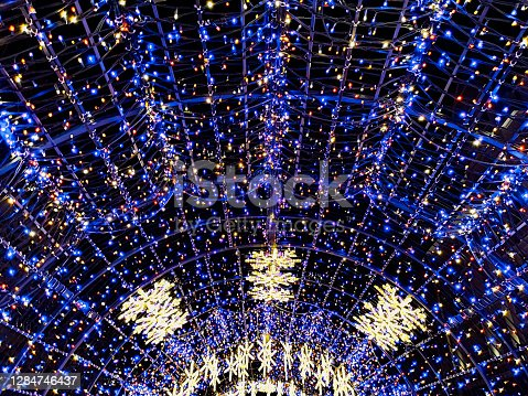 Round colorful christmas tunnel made of christmas lights in city streets