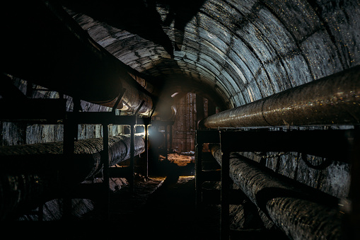Round concrete underground tunnel of heating duct system with rusty pipes.