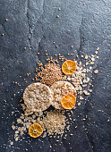 Round Crisp on a black stone background. Rice grains, oatmeal flakes and buckwheat series. Fruit top.
