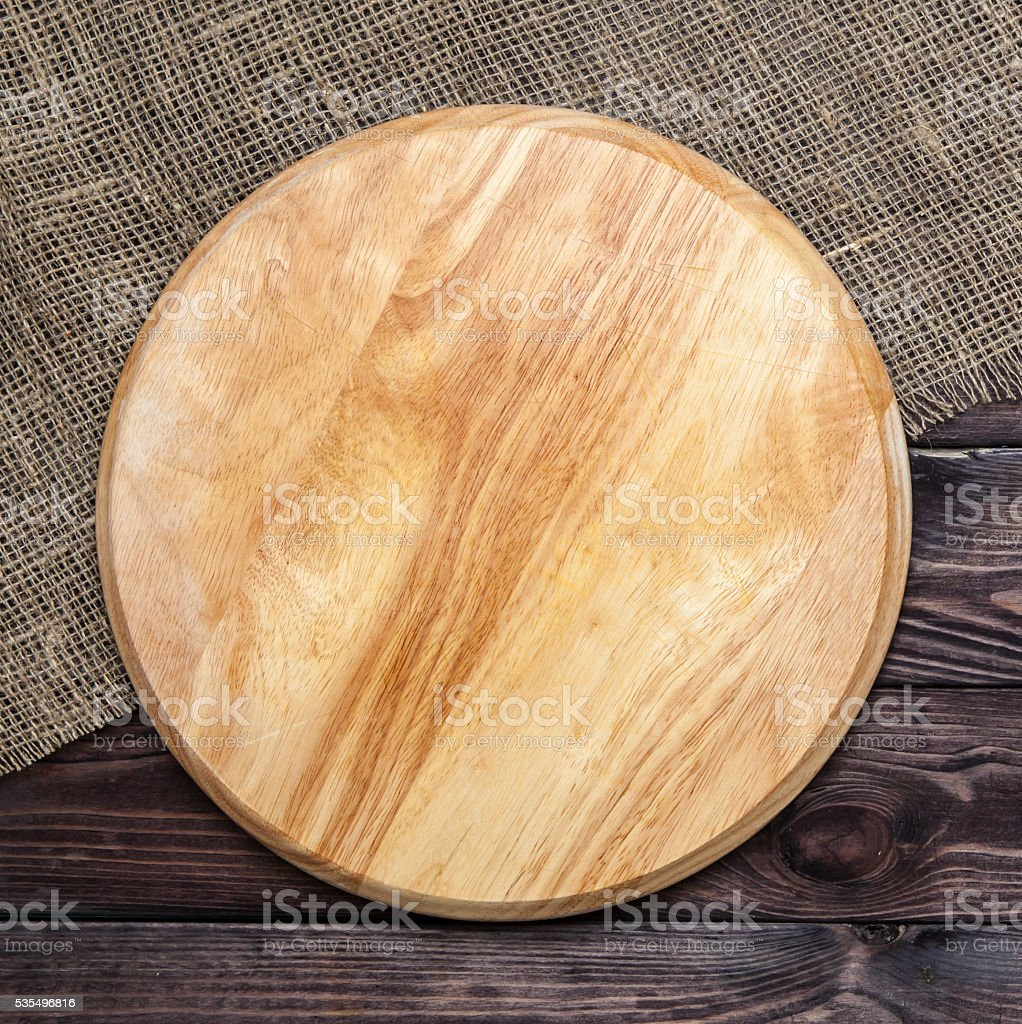 Round cutting board on a wooden table, top view stock photo