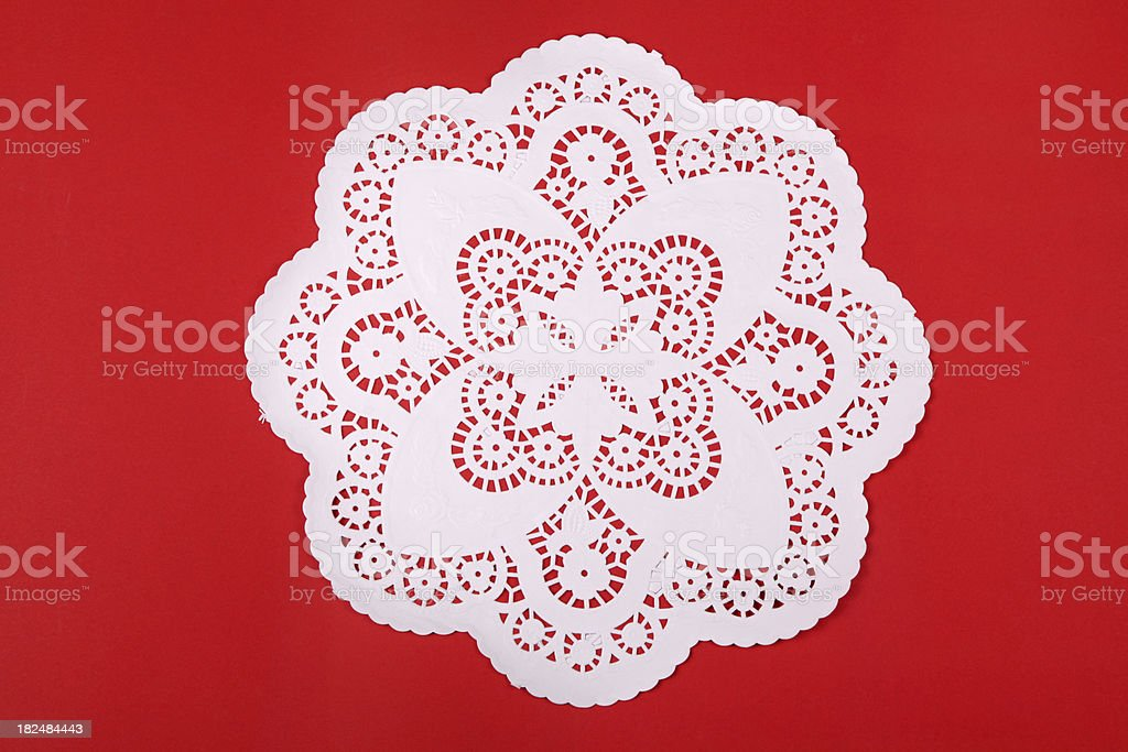 Round doily on red cardboard royalty-free stock photo