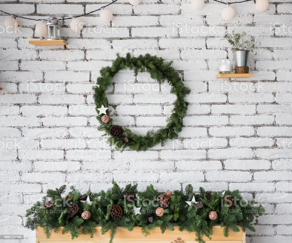 round elegant christmas wreath hanging on white brick wall stock photo more pictures of ball. Black Bedroom Furniture Sets. Home Design Ideas