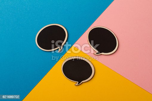 istock Round empty chalk board speech bubbles on colored papers 621689702