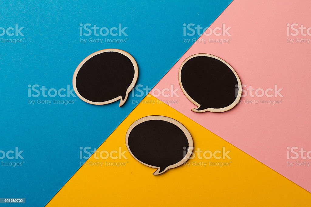Round empty chalk board speech bubbles on colored papers stock photo