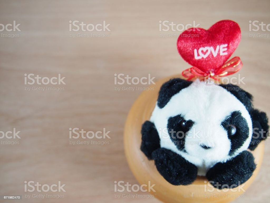 Round fat panda in baked clay jar, love on red heart pillow stock photo