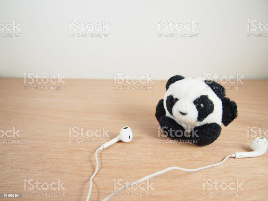 Round fat panda with white earphones stock photo