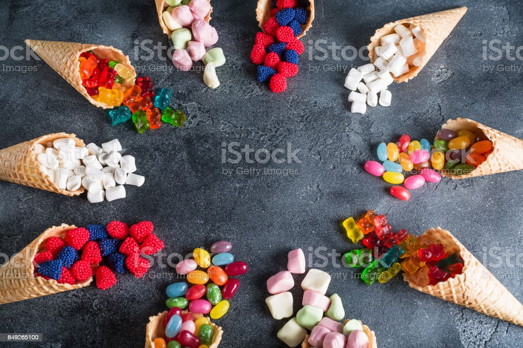Round frame made of colorful bright assorted candy in waffle cones. Sweety food. Flat lay, top view stock photo