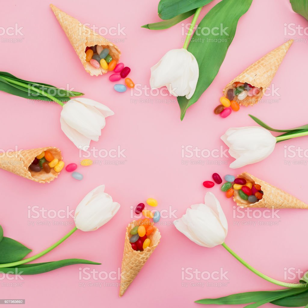 Round frame made of colorful bright candy in waffle cones and white flowers on pink background. Flat lay, top view Round frame made of colorful bright candy in waffle cones and white flowers on pink background. Flat lay, top view Blossom Stock Photo