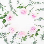 istock Round frame made of pink flowers and eucalyptus branches on white background. Flat lay, top view. Valentine's background 847825292