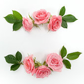 istock Round frame made of pink roses, green leaves, branches, floral pattern on white background. Flat lay, top view. 824994968