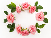istock Round frame made of pink roses, green leaves, branches, floral pattern on white background. Flat lay, top view. 824995008