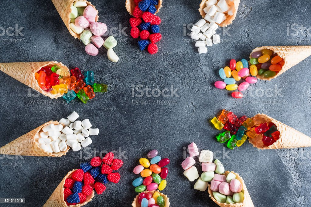 Round frame of bright assorted candy in waffle cones. Sweety food. Flat lay, top view stock photo