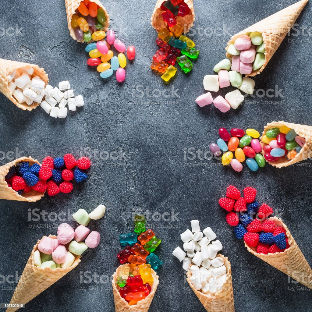 Round frame of colorful bright assorted candy in waffle cones on dark background. Flat lay, top view stock photo