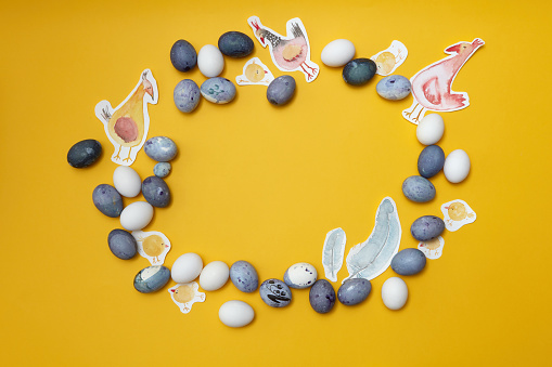 Easter wreath with Painted chickens and easter eggs in round shape on yellow background