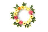 istock Round frame with roses and green leaves isolated on white background. Flat lay, top view 827021294
