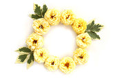 istock Round frame with yellow roses and green leaves isolated on white background. Flat lay, top view 827021260