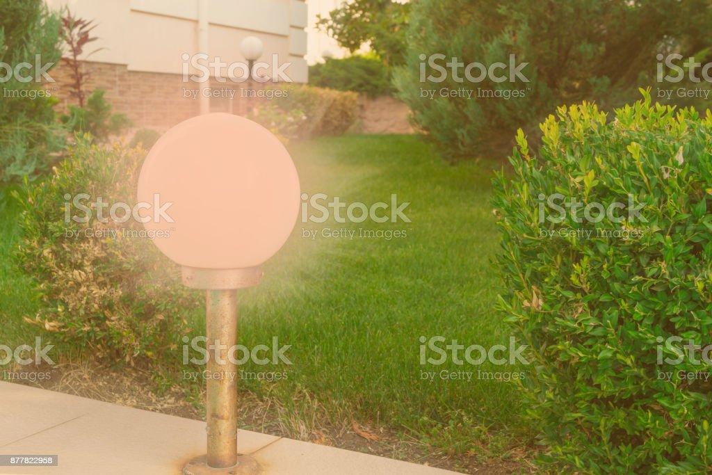 Round garden lantern next to the lawn near the house stock photo