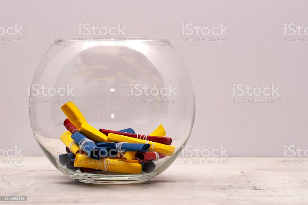 A round glass jar with colored notes of craft paper. Light background
