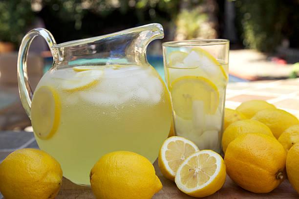 Round glass jug of fresh lemonade with sliced lemons at pool stock photo