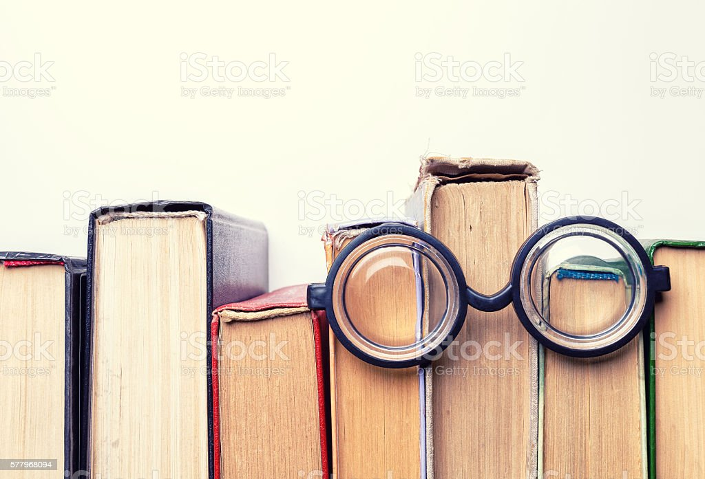 round glasses lay on top of a  battered old books. stock photo