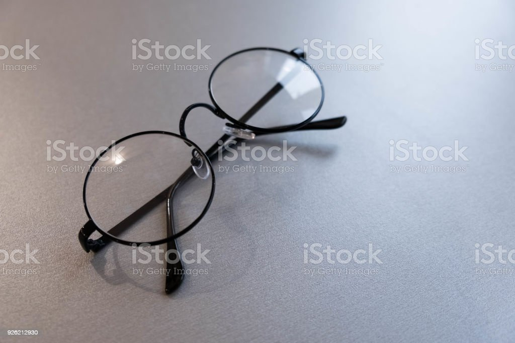 Round glasses with transparent lenses. vintage old glasses on a gray background stock photo