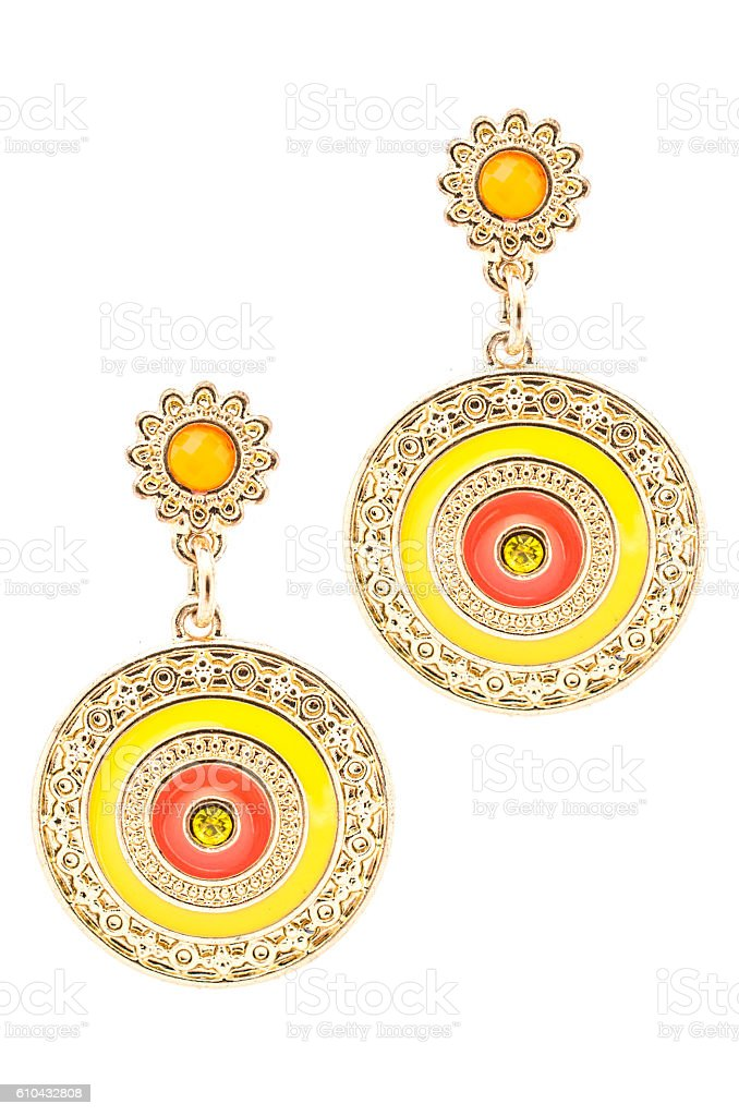 Round gold earrings inlaid with  gemstones on a white background stock photo