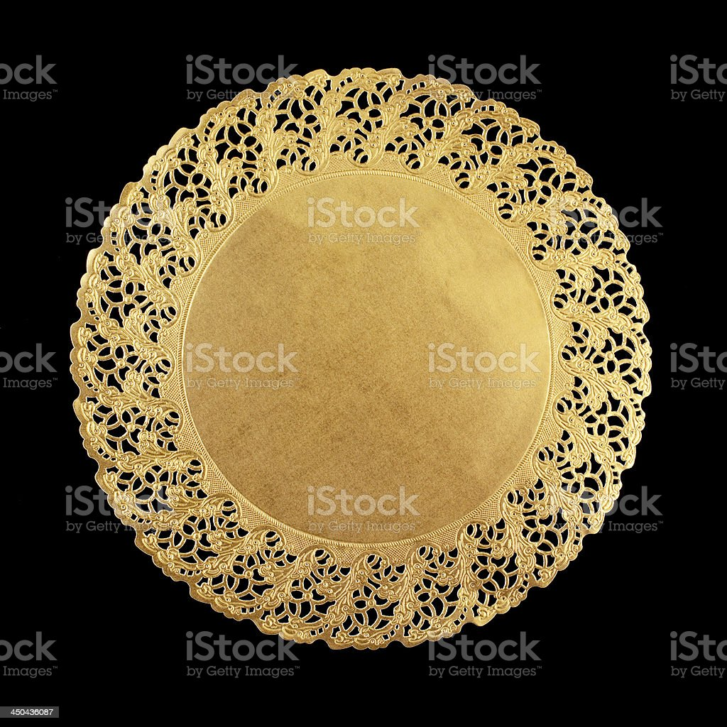 Round golden doily on black background stock photo