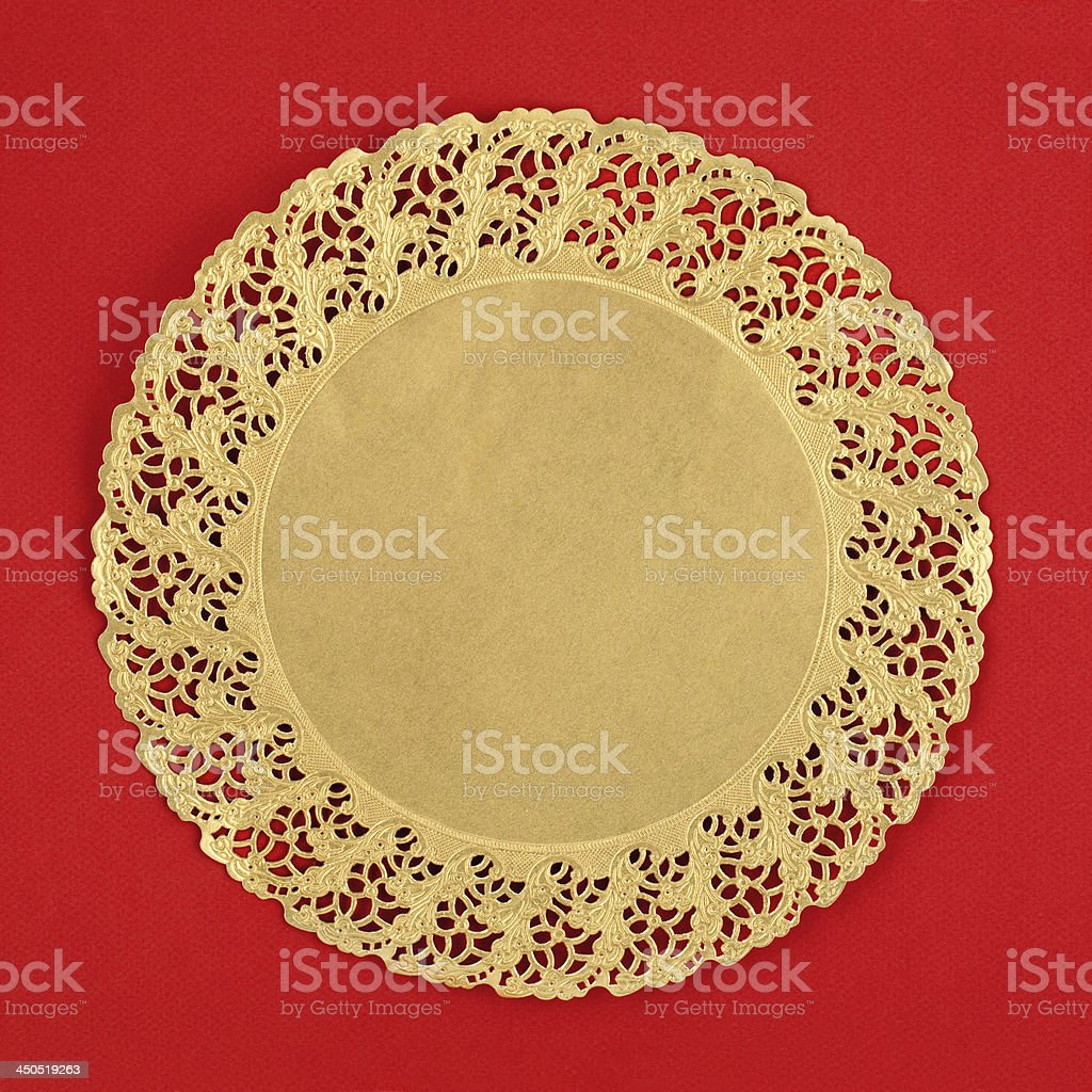 Round golden doily on red background stock photo