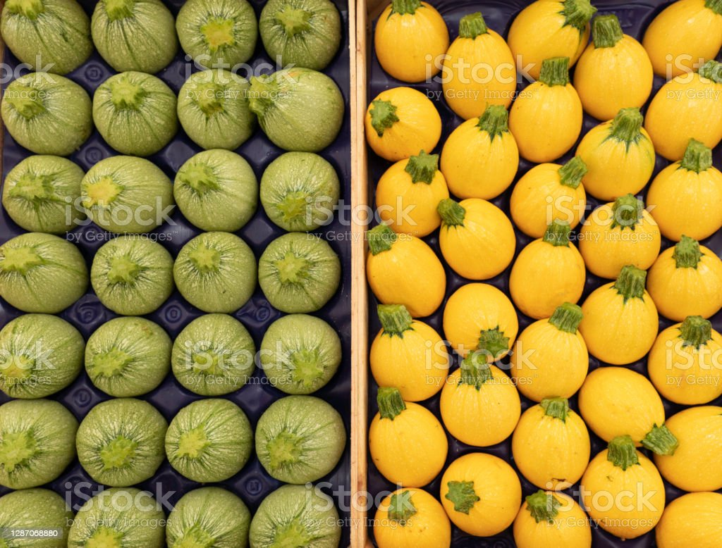 Round green and yellow zucchini on a market stall green and yellow round zucchini lined up Agriculture Stock Photo
