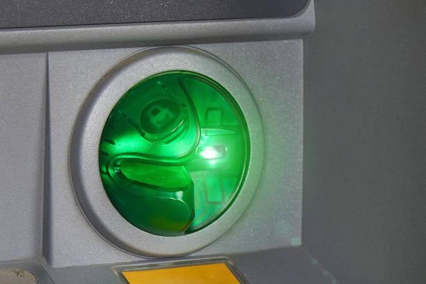 Runder grüner Geldautomat für Debit- und Kreditkarten-Nahaufnahme. Grüne Hintergrundbeleuchtung. Sichere Back-Office-Transaktionen, Geldüberweisungen, Bargeldabhebungen, Bezahlung von Dienstleistungen und Waren online. – Foto